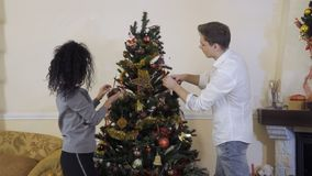 Young guy with girlfriend decorates Christmas tree