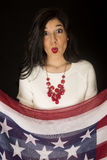 Beautiful woman with her lips puckered holding stars and stripes Royalty Free Stock Photography