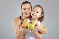 Beautiful woman and her little daughter with fresh fruits stock photo