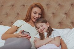 Beautiful woman and her little daughter using smart phone royalty free stock photography