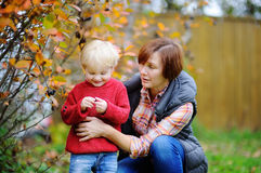 Beautiful woman and her little grandson enjoying black currants Stock Photo