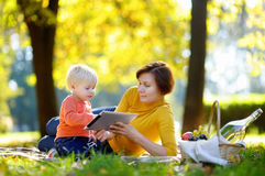 Beautiful woman and her little grandson having a picnic in park Stock Photo
