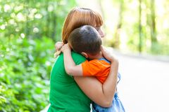 Beautiful woman and her little son. Beautiful women and her little son trembling and strongly embracing, on city park background. Summer portrait of mother and stock photo