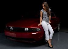 Beautiful woman and her sports car. A beautiful young woman leans on the hood as she admires her red sports car in the shadows Stock Photography