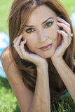 Beautiful Woman In Her Thirties. Outdoor portrait of a beautiful young brunette woman in her thirties relaxing on her hands Royalty Free Stock Photography
