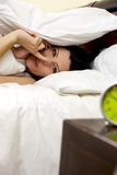 Beautiful woman hiding in bed makes silence sign under blanket Stock Photos