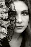 Beautiful woman hiding behind fan stock photo