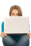 Beautiful woman hiding behind a laptop Stock Photo