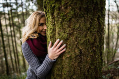 Beautiful woman hiding behind tree trunk in forest. Portrait of beautiful woman hiding behind tree trunk in forest Stock Photography