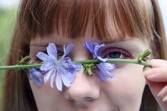 Beautiful woman hiding eye with wildflower Royalty Free Stock Image
