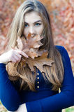 Beautiful woman hiding face behind autumn brown leaf Royalty Free Stock Image