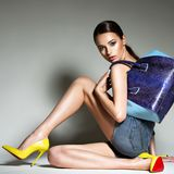 Beautiful woman in high heels holds handbag. Fashion young girl with long legs, naked body posing at studio Stock Image