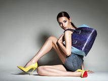 Beautiful woman in high heels holds handbag. Royalty Free Stock Image