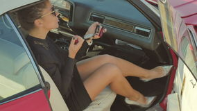 Beautiful woman on high heels paints the lips with lipstick in a retro car stock video footage