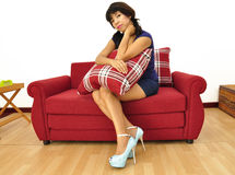 Beautiful woman short dress sits on red sofa Royalty Free Stock Images
