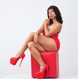 Beautiful woman in high heels sits on red stool Royalty Free Stock Photography
