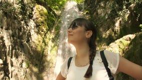 Woman near waterfall enjoying nature stock video footage