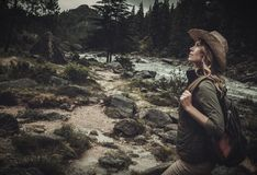 Beautiful woman hiker near wild mountain river. Royalty Free Stock Images