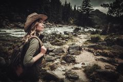 Beautiful woman hiker near wild mountain river. Royalty Free Stock Photography