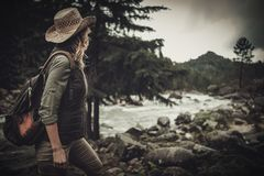Beautiful woman hiker near wild mountain river. Stock Photos
