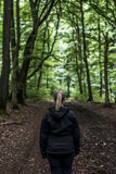 Beautiful woman hiker standing on forest trail looking away. Female on hike in nature spooky mystical forests. Beautiful woman hiker standing on forest trail and stock photo