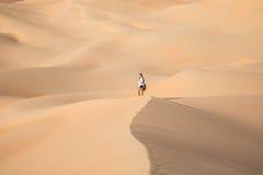 Beautiful woman hiking on giant sand dunes. Liwa desert, UAE Stock Image