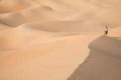 Beautiful woman hiking on giant sand dunes. Liwa desert, UAE Stock Images