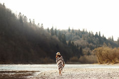 Beautiful woman hipster walking on river beach in mountains,wear Royalty Free Stock Image