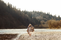 Beautiful woman hipster walking on river beach in mountains, wear royalty free stock photo