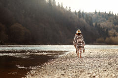Beautiful woman hipster walking on river beach in mountains, wearing hat and poncho, boho travel concept, space for text. Beautiful woman hipster walking on royalty free stock image