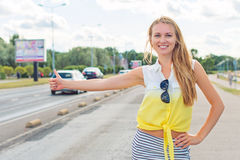 Beautiful woman hitch-hiking. Royalty Free Stock Images