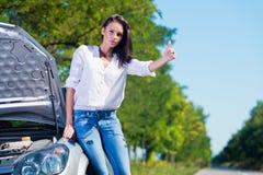 Beautiful woman hitchhiking. By a broken car Stock Photos