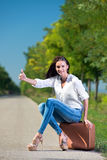 Beautiful woman hitchhiking. With suitcase Royalty Free Stock Photography