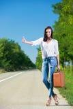 Beautiful woman hitchhiking. With suitcase Stock Photo