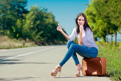 Beautiful woman hitchhiking. With suitcase Royalty Free Stock Photos