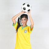 Beautiful woman hold ball over her head with wearing Brazil foot Stock Images