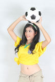 Beautiful woman hold ball over her head with wearing Brazil foot Royalty Free Stock Images