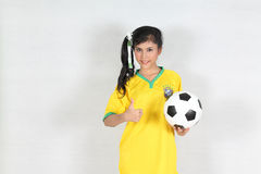Beautiful woman hold ball and thumbs up with wearing Brazil foot. Image Beautiful woman hold ball and thumbs Up with wearing Brazil football top Royalty Free Stock Photography