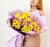 Beautiful woman hold bouquet of chrysanthemum flowers yellow and purple on white Stock Images