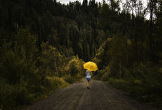 Beautiful woman hold yellow umbrella and walks on a country road under rain.  Stock Images
