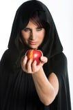 Beautiful woman holding apple. Beautiful seductress holding apple with black cloak Stock Image