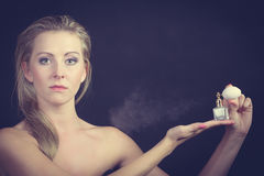 Beautiful woman with holding and applying perfume Royalty Free Stock Image