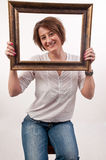 Beautiful woman holding around her face a frame and looking thro Royalty Free Stock Photography