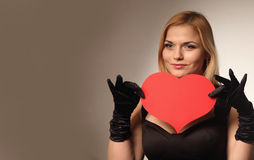 Beautiful woman holding artificial heart. Woman holds big red heart love symbol Royalty Free Stock Image