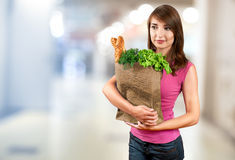 Beautiful woman holding a bag of groceries Royalty Free Stock Image