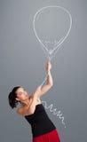 Beautiful woman holding balloon drawing. Beautiful young woman holding balloon drawing Royalty Free Stock Image