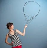 Beautiful woman holding balloon drawing. Beautiful young woman holding balloon drawing Royalty Free Stock Photos