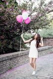Beautiful woman holding balloons outdoors. Romantic Stock Photo