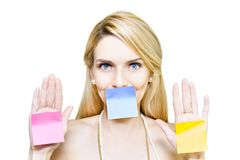 Beautiful woman holding blank message sticky paper. Funny isolated studio portrait of a an attractive young blond woman holding 3 colourful blank sticky notes Stock Photos