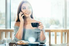 Beautiful woman holding blue cup of coffee and talking by mobile phone. royalty free stock photos